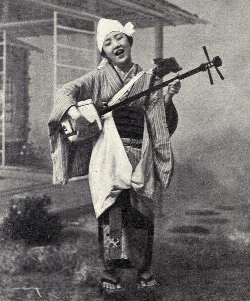 Playing the shamisen in 1899 Japan. Image via Pinterest