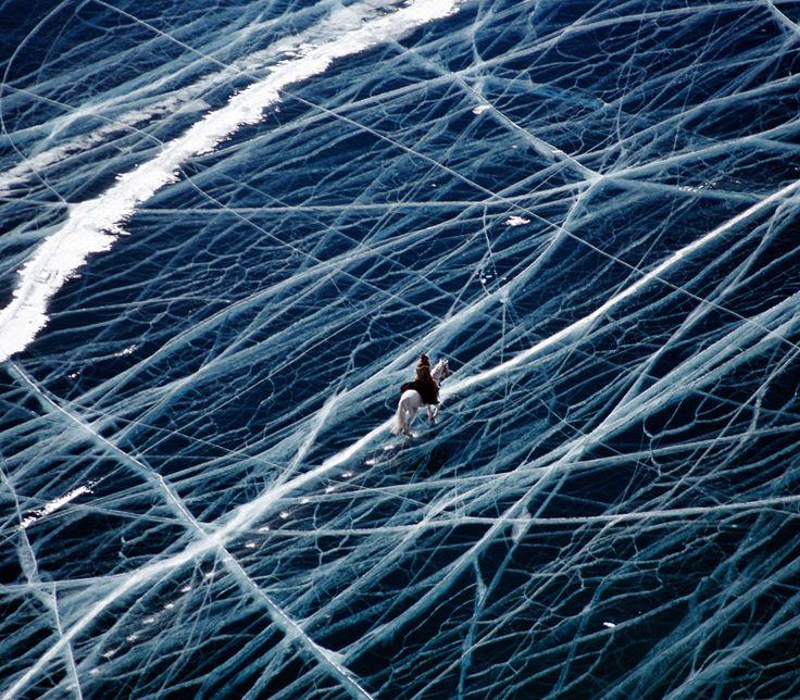 Riding a horse across a frozen lake in the Pamir mountains