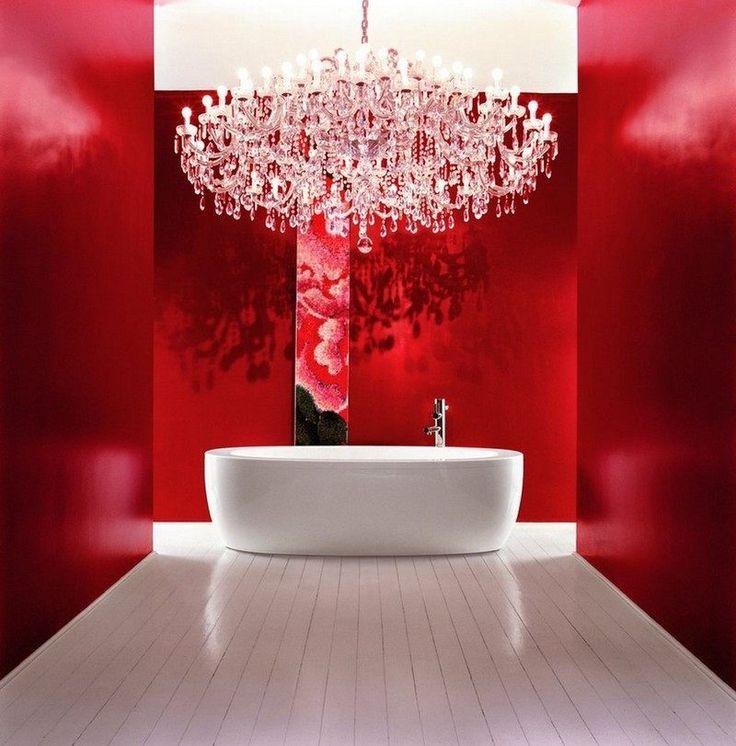 salle de bains moderne avec une peinture murale rouge, baignoire îlot blanche et un grand lustre en cristal