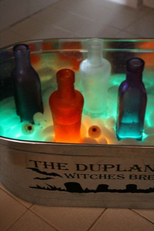Easy Halloween party decor ideas: Give your drink station a swamp-gas effect by adding glow sticks (and sticky eye balls!) to the ice.