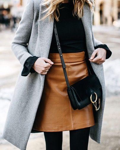 Gray coat, black turtleneck, camel leather skirt, black leggings, black crossbody bag.