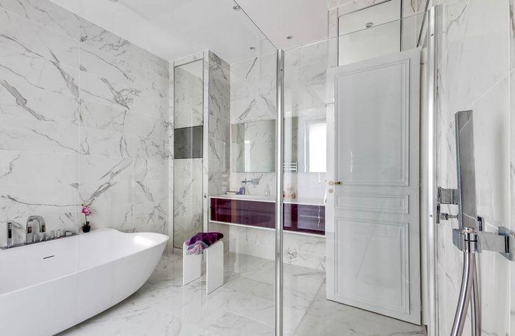 Une salle de bains en marbre blanc, réveillé par le meuble aubergine.