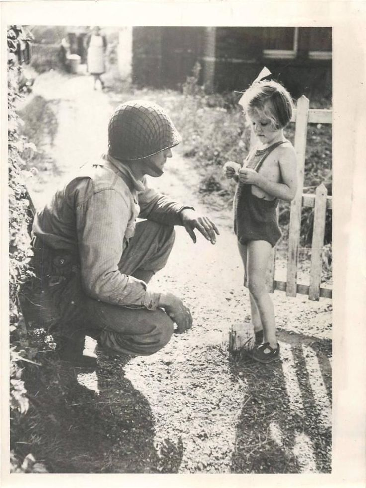 1943- U.S. soldier makes friends with a little girl during a lull in joint exercises held by British and American forces somewhere in England.
