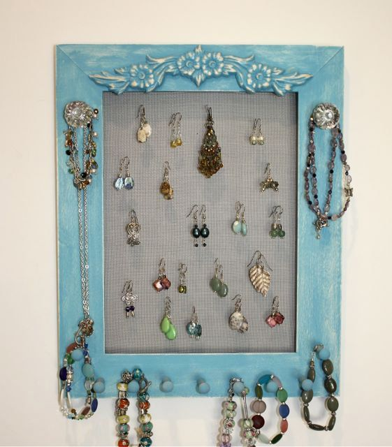 A Turquoise Jewelry Frame with a screen area of 9x12 which can easily hold 35 pairs of Earrings, on the wall.    Wood frame painted a wonderful turquoise, added a large floral wood applique added for detail and style.    Knobs are clear glass with a brushed nickel base, screwed into the frame, strong enough to hold heavy necklaces.    Matching pegs along the bottom will take care of all your jewelry needs.    Always makes a great gift for any occasion.    Frame has sawtooth hangers in each…