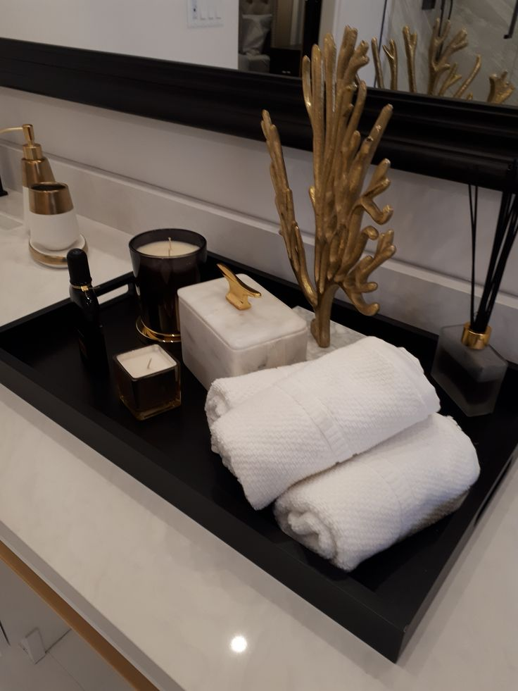 Beautiful bathroom decor. We love this black tray with gold and marble accents. The white towels add such a clean feeling.