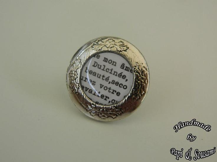 Στρογγυλό δαχτυλίδι ρητίνης σε ασημί πλαίσιο με απόσπασμα από τον Δον Κιχώτη, που ανοίγει για να βάλετε αγαπημένα memorabilia μέσα του-Round resin photo frame locket ring in silver tone with an excerpt of Don Quichotte