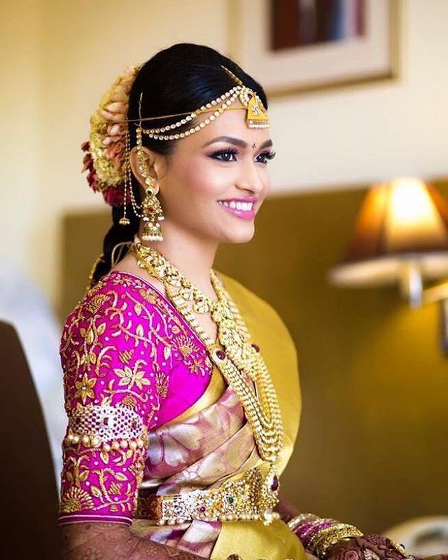 South Indian bride. Gold Indian bridal jewelry.Temple jewelry. Jhumkis.Gold silk kanchipuram sari with contrast pink blouse.braid with fresh jasmine flowers. Tamil bride. Telugu bride. Kannada bride. Hindu bride. Malayalee bride.Kerala bride.South Indian wedding.