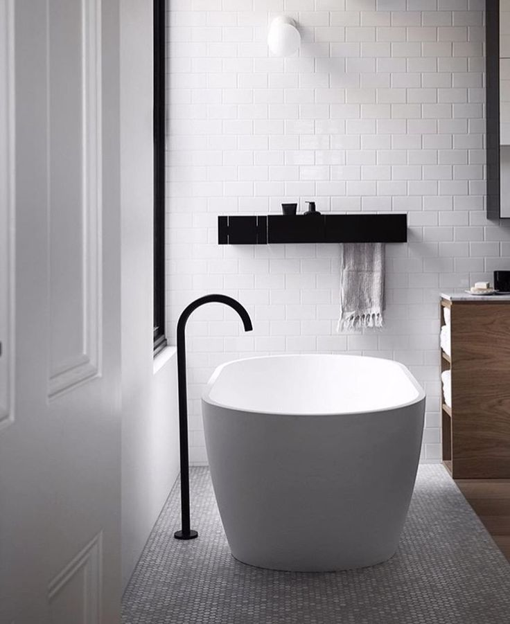 modern black and white bathroom design with subway tiles from floor to ceiling touches of black and a mix with wood