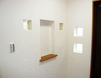 ニッチの両側にガラスブロック、玄関ドアにヨコスベリ窓を並べて、とてもオシャレで明るい玄関になりました。
