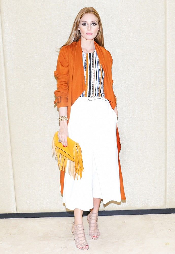 Olivia Palermo in a Zara striped top, orange trench, Tibi culottes, yellow fringe clutch, and nude strappy heels