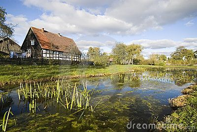 Picturesque rural village in Poland. Typical Polish retro countryside. Cottage and pond in autumn, sunny weather.
