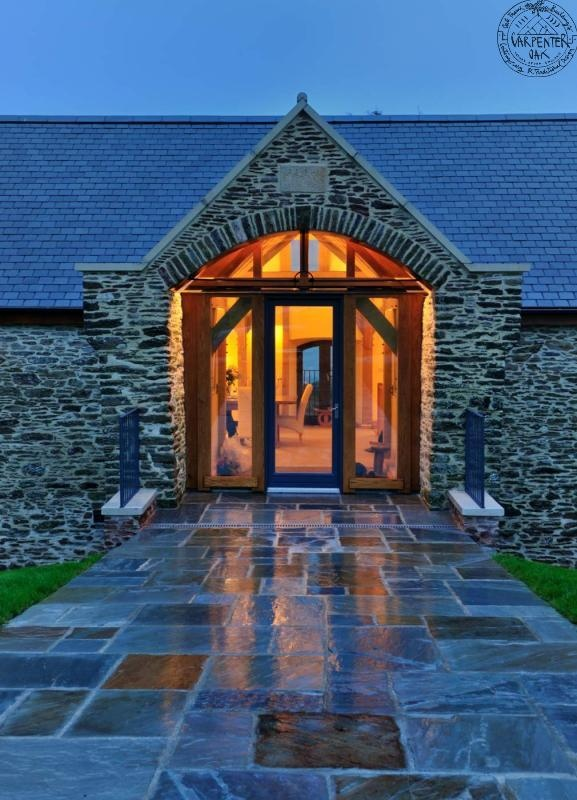 Entrace by night at Beautiful barn conversion in Devon, England designed by architect Roderick James | Carpenter Oak.