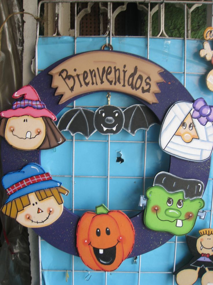 Halloween door wreath with five faces: witch, scarecrow, jack o lantern, frankenstein, and a mummy and one hanging bat piece.