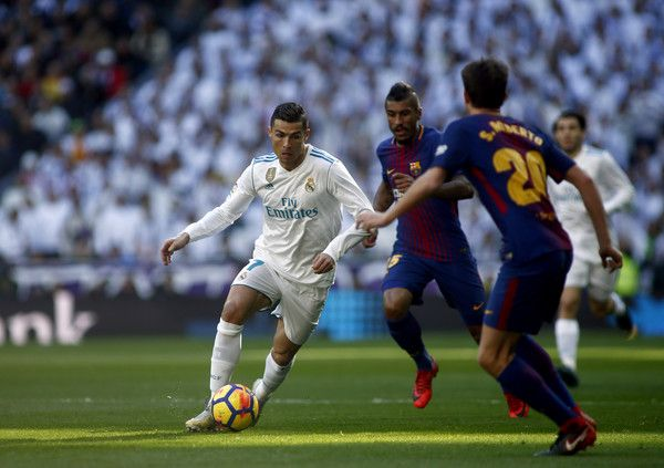 """Real Madrid's Portuguese forward Cristiano Ronaldo runs with the ball during the Spanish League """"Clasico"""" football match Real Madrid CF vs FC Barcelona at the Santiago Bernabeu stadium in Madrid on December 23, 2017.  / AFP PHOTO / OSCAR DEL POZO"""