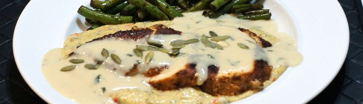 ancho crusted chicken breast atop green-chile-goat-cheese grits topped with a cilantro cream sauce & roasted pepitas (pumpkin seeds)