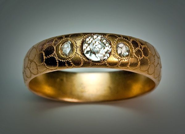 An Antique Wedding Ring. This gold and diamond men's wedding band was made in St Petersburg, Russia, between 1904 and 1908. The matte gold surface of this highly unusual antique wedding ring is covered with stylized circular patches with zig zag borders. The engraved zig zags reflect light and stand out on the matte surface of the ring.