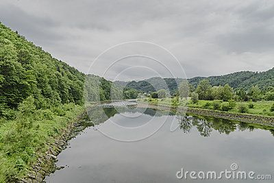 Dunajec river in small village Rożnów  in Poland . View from the foodbridge on river and mountains with forest.