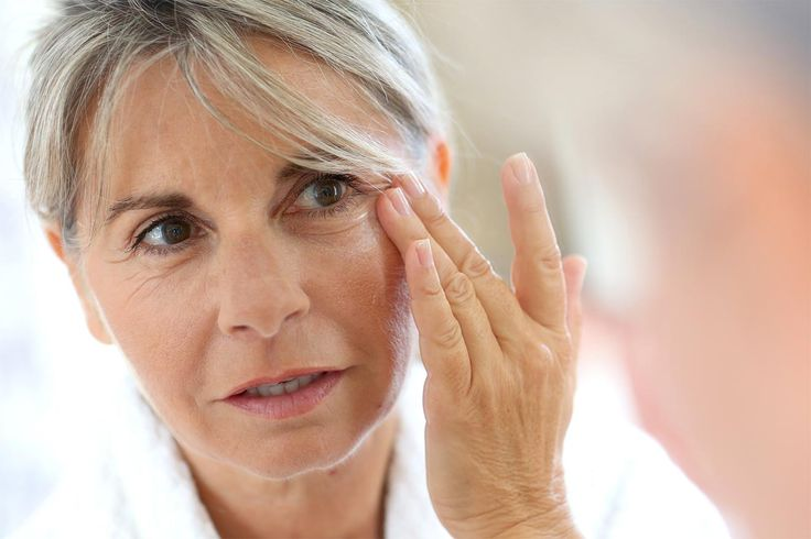 Older woman looking in the mirror touching her bottom eyelid.