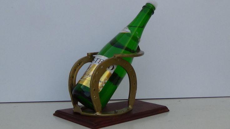 Porta botella de vino con 4 herraduras y base en madera con terminado en tinte.