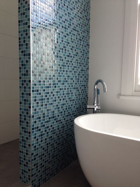 A bathroom renovation in Mt Eden. Working with a natural floor tile and white gloss on the walls we introduced a teal mosaic wall to make this a colourful children's bathroom #bathroom #tiles #mosaic #independentceramics #bath #shower #white #gloss #designer #interiordesign