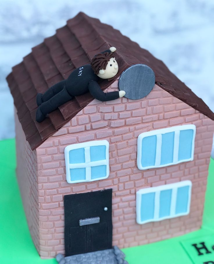 Hand carved house shaped cake with Sky TV engineer on the roof changing a Sky dish