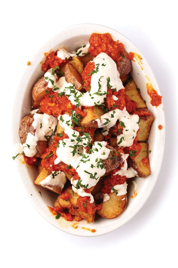 From SAVEUR issue no. 165 At Barcelona's Bar Mut, crisp skin-on potatoes are blanketed in mayonnaise and a thick spicy tomato sauce.