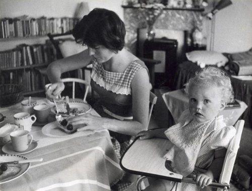Moeder geeft een peuter te eten die in een kinderstoel aan tafel zit. Nederland, plaats onbekend, 1960