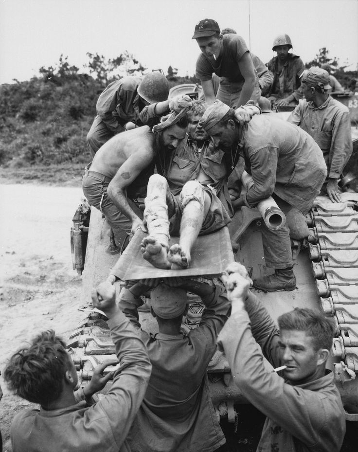 Okinawa 1945: Rescuers remove a wounded buddy from a tank disabled by Japanese fire.