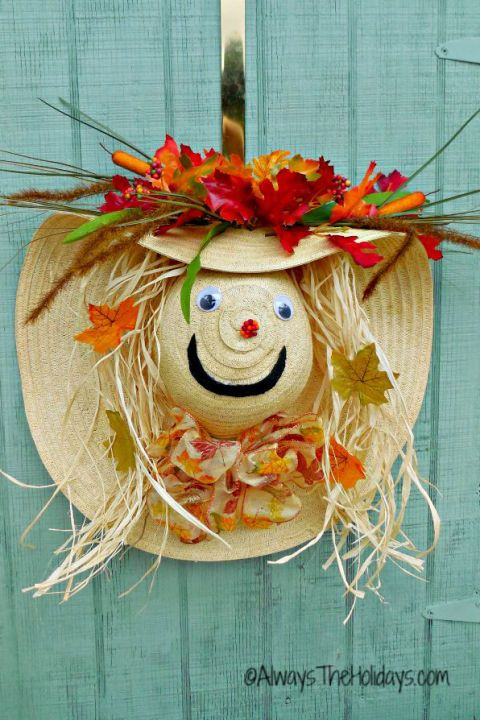 Turn a floppy straw hat with a wide brim into a cute scarecrow that will greet guests with a friendly face. This fall door decoration is so much cuter than your usual wreath!