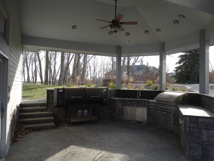 """This contains the grilling area of our outdoor kitchen. This contains an oversized wood pellet grill for hog roasting and another 54 """" gas grill. This is a covered space that opens to a poolhouse kitchen and bar and above is an in ground fire pit. Outdoor sink for convenience. Granite counters and surfaces."""