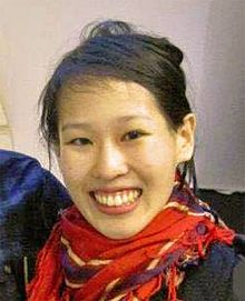 A smiling Asian woman wearing a red scarf and black coat