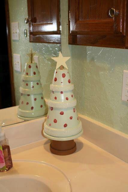 4 aardewerken bloempotjes (die misschien nog vergeten in je schuur liggen) wit verven met rode stippen (kan natuurlijk ook een andere kleur zijn) een witte houten ster maken of kopen en je hebt je eigen kerstboom.
