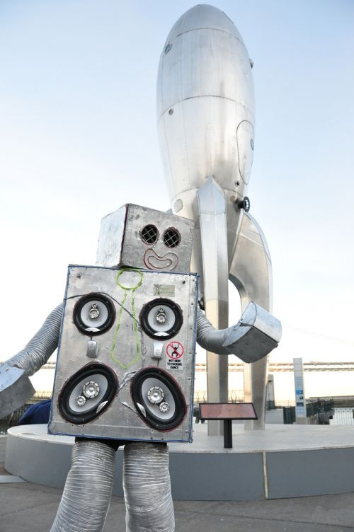 """In 2011 a single robot [...] armed with only four speakers and a dream, [...] encouraged others to dance to the music eminating from his very being. Full on dance parties ensued. However, he was only one robot and could only do so much. Next year he will have friends.""—Robot Dance Party"