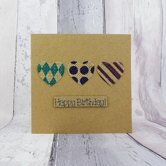 Recycled Kraft Happy Birthday card with three printed hessian jute burlap hearts featuring three geometric prints in purple, blue and green. This handmade heart birthday card would be a lovely card for an environmentally conscious recipient or someone who likes rustic country style. With neutral colours this would make a great card for her or a card for him.  The pattern on the hearts are stripes, circles (large dots) and harlequin diamonds. The sentiment on this recycled kraft birthday card…