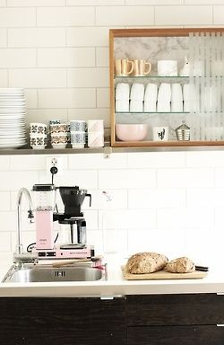 gold mugs, crockery collection, and simple free-standing glass shelf cabinet for extra storage via pink wallpaper