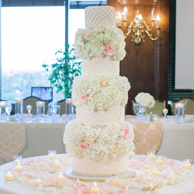 Elaborate white wedding cake with large pink & white floral arrangements between layers | Mariel Hannah Photo | Anamie's Sweets