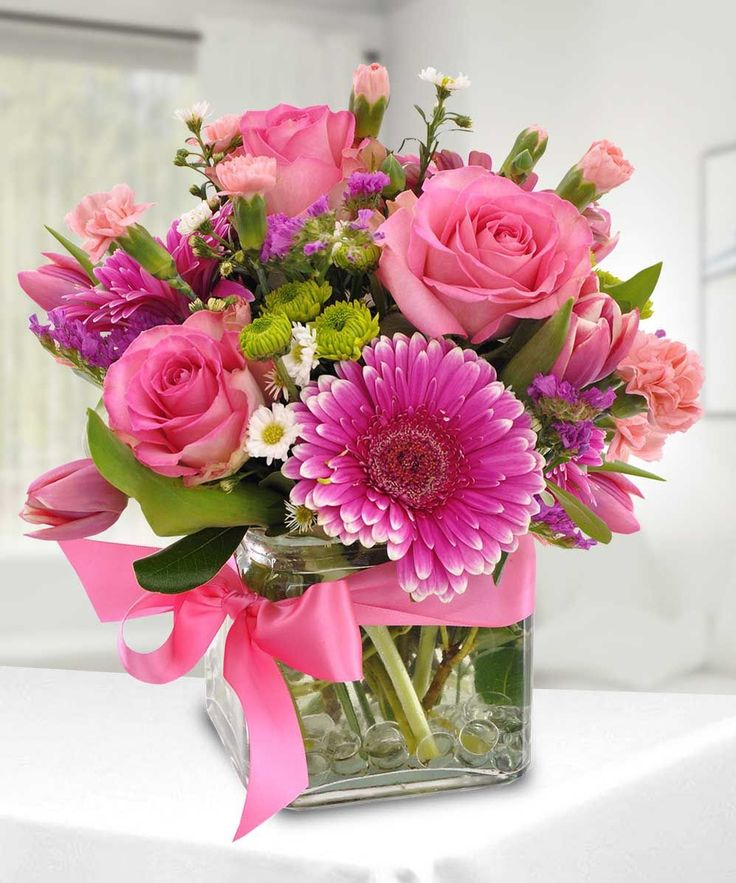 "Offer a bouquet blooming with a ""fresh from the garden"" appeal. Pink roses, carnations, mini carnations, and gerbera daisies are accented with lush greens. Gorgeously arranged in a clear glass cube vase accented with a pink satin ribbon,..."