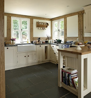 windows, sink, like the cabinets, dark floor and countertops, island with wood, low ceilings with small lights