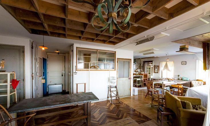 天井にも古材を 杉並区の住宅地に建つ築20年のマンションを、リノベーションして住む多治見武昭さん。アンティーク家具が似合う空間は、すべてリノベーションをしてしまうのではなく、敢えて所々に前のオーナーが住んでいた時の息遣いを残しながら、多治見さんのセンスや好きなものを加えていく方法で作られている。多治見さんが好きなアンティーク家具の、長い年月を経て刻み込まれた傷や味わいと、しっくり馴染んでいる。 たとえば床。ヘリンボーンに貼られた部分、足場板やタイルなど、様々な床材が混在している。 「リノベーションの際、部屋を仕切る壁を壊して大きな空間を作りました。床はその場所ごとに張り方が違っていたのですが、敢えてそのまま残した場所もあります」 床材が、クラシックなヘリンボーンだったり、柔らかな印象の足場板だったりと、場所によって表情が変わる。 正方形のコンクリートブロックと白いカーテンで、ゆるやかにリビングの空間を分けている。 サッシの内側は色を白に塗り替えた。白いカーテンの裾の一箇所を上に留めて、表情のある窓を作る。 天井の一部に古材をスクエアに貼り、空間にニュアンスを演出。…