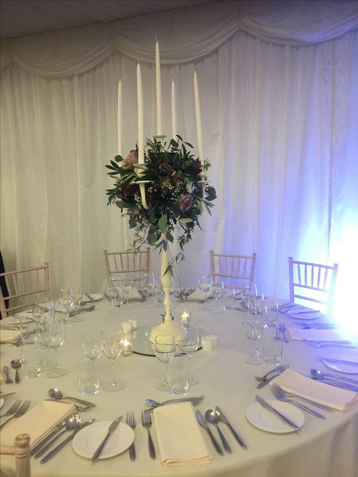 White Dress Candelabra: Olive Leaf, Amnesia Rose, Gypsophila, Wax Flower, Eucalyptus, White Veronica, Burgundy Skimmia, White Thistle