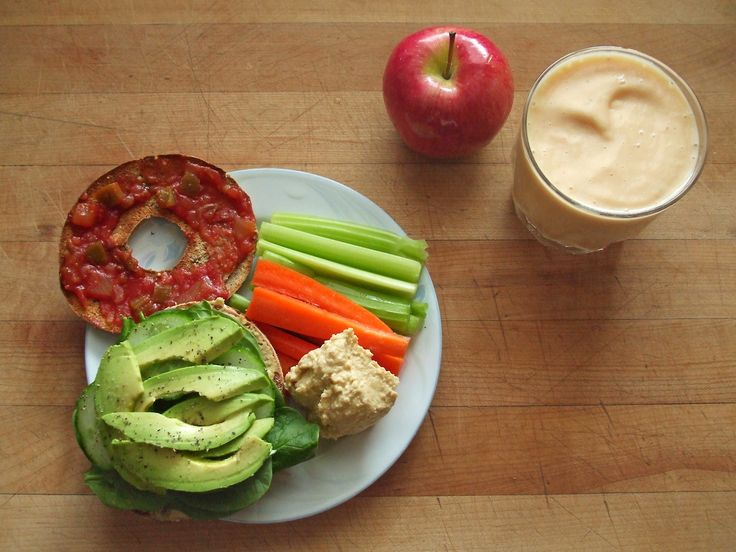 thin multigrain bagel sandwich with salsa, hummus, avocado, cucumber, spinach, salt, and pepper, celery and carrots with hummus, an ambrosia apple, and a mango-banana-soy milk smoothie