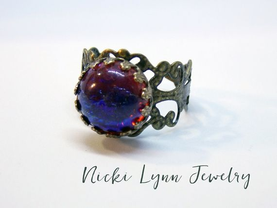 Stunning, beautiful, gorgeous! These are just some of the words that describe this ring. This one of a kind Dragon Breath Czech glass opal is a fiercered with fire of blue... #adjustable_ring #art_nouveau_ring #bead_ring #czech_glass_ring #filigree_ring #gift_for_her #jewelry #large_cocktail_ring #renaissance_ring #ring #steampunk_ring #victorian #victorian__earrings #victorian_jewelry #victorian_ring