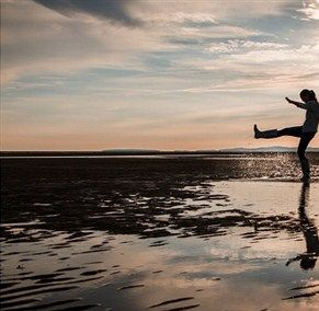 Tansy dances and flips at the ocean shore after meeting Jamie for the first time