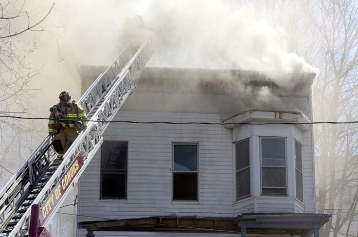 Cohoes firefighters descend from the aerial tower as they battle fire at 10 Younglove Avenue, Monday, April 8, 2013 in Cohoes. (J.S. Carras/The Record)