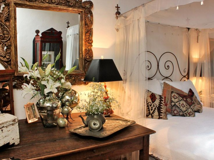 In this Mexican-influenced bedroom, sheer white curtains hang from the top of a canopy bed made with white sheets and decorated with dark-colored patterned pillows. An ornate wood mirror hangs on the wall, and a side table is decorated with flower bouquets.