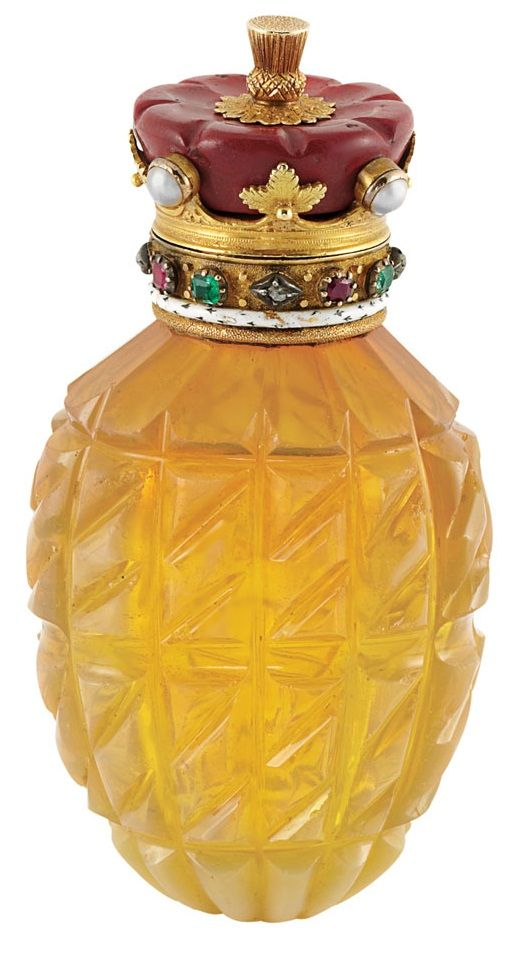 Antique Perfume Bottle. The ribbed carved opalescent glass bottle with a stylised crown topper composed of carved jasper, further topped by a gold knob, edged by 4 split pearls spaced by gold leaf panels, surmounted by a ring of alternating rectangular-cut rubies and emeralds and rose-cut diamonds, accented by a band of white enamel with black accents, engraved on inside hinged cover Souvenir de la Marechale Gourko 1906, circa 1900.