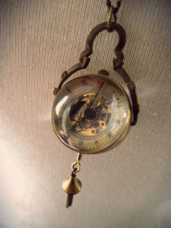 A glass dome pendant.  Brass detail with a chain tassel hanging from the watch.  It is a wind up watch. The length of the chain is 19 inches or