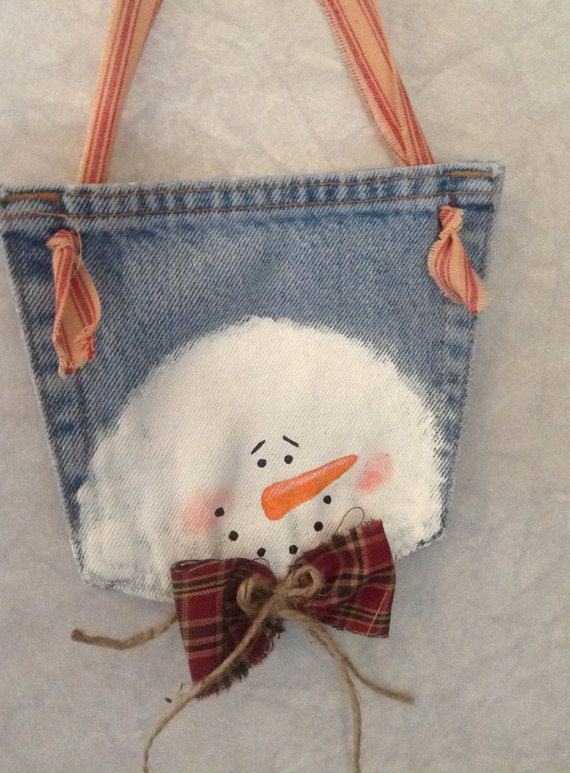 A primitive snowman hanging Christmas ornament hand painted on a recycled denim jean pocket. Snowman is wearing a green or red homespun fabric bow with an additional twine bow on top. Hangs with a strip of red ticking fabric. Hang on your tree, door knob, or wall. Adult size jean pocket has been used. Ready to ship. Select color of bow desired, red plaid or green/cream check.