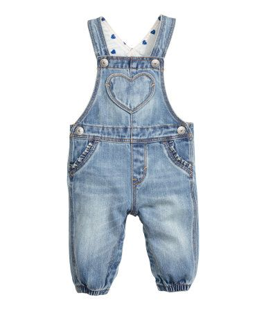 Bib overalls in soft washed cotton. Adjustable straps with snap fasteners, snap fasteners at sides and gusset, and elasticized hems. Heart-shaped bib pocket, mock front pockets with ruffle trim, and regular back pockets.