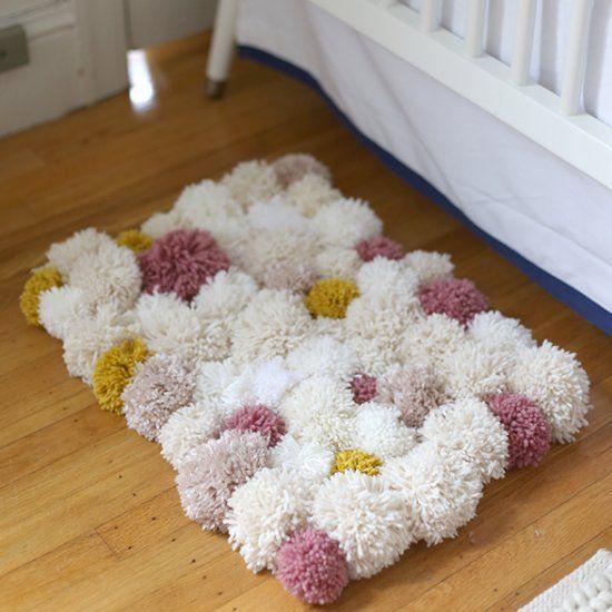 Make a pretty, lush bedside rug made of pom poms!